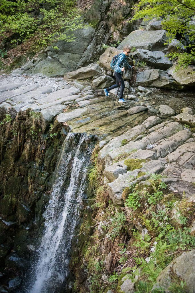 Ein schmaler Wanderweg quert einen Wasserfall.