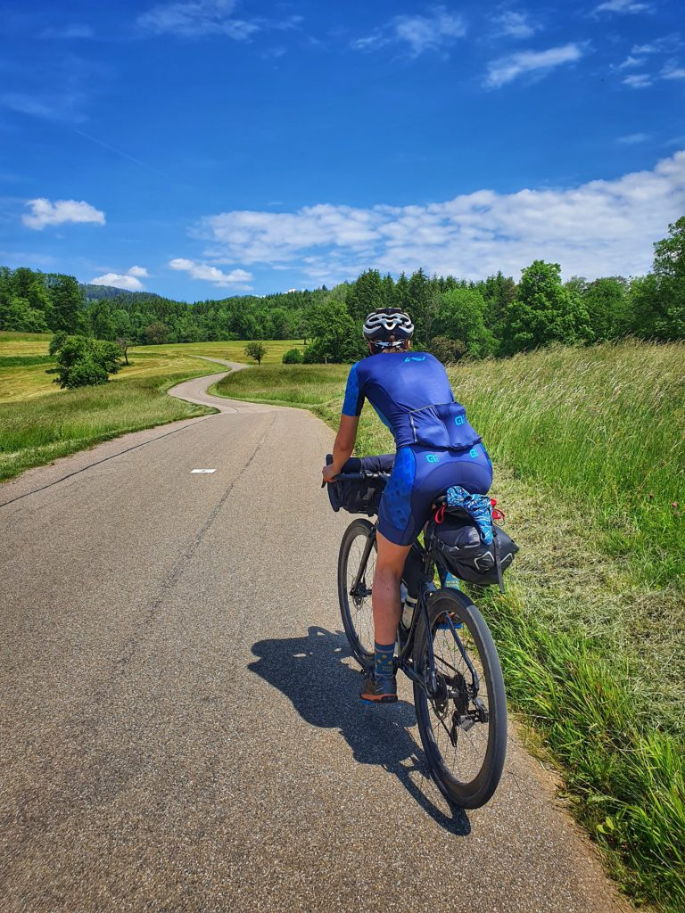 Radfahrerin auf kurviger Straße im Schwarzwald